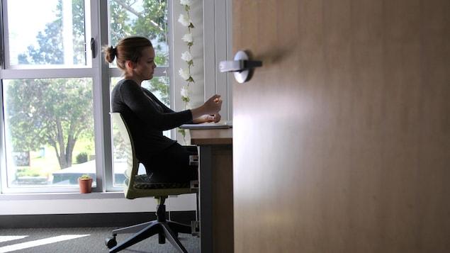 Assise à son bureau, une étudiante suit un cours en ligne de chez elle avec une fenêtre en arrière-plan.