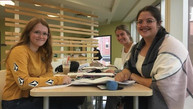 Des jeunes femmes assises autour d'une table sur laquelle il y a plusieurs livres.