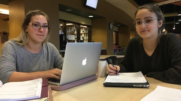 Deux étudiantes assises autour d'une table avec leurs ordinateurs.