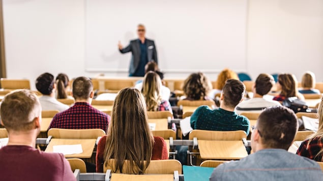 Un professeur s'adresse à une classe où sont assis de nombreux étudiants.