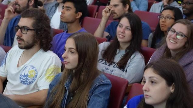 Des étudiants écoutent le chef péquiste en souriant.