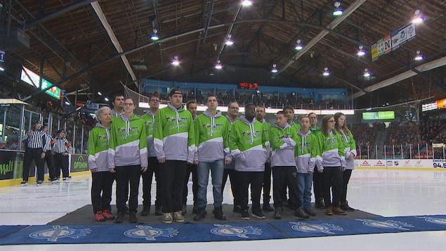 Un groupe de personnes au milieu d'une patinoire de hockey