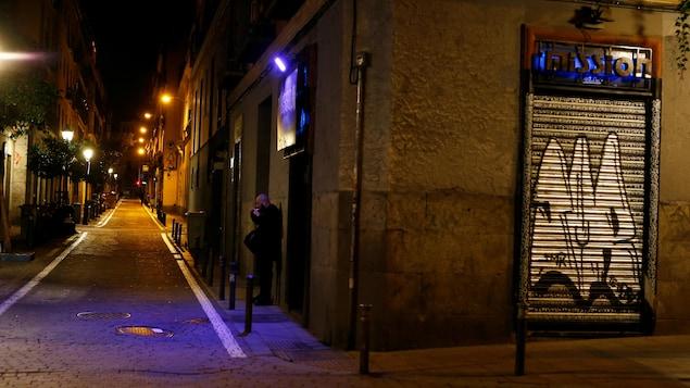 Un homme fume une cigarette seul dans une ruelle déserte.