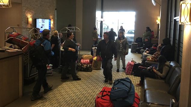 Des gens avec leur valise dans le hall d'entrée d'un hôtel.