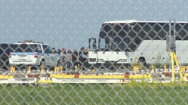 Des évacués embarquent dans un autocar.
