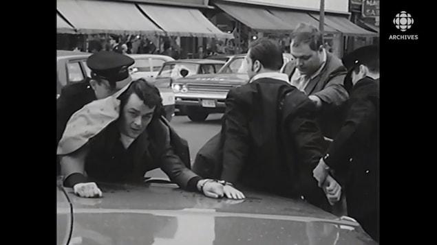 Richard Blass en état d'arrestation, les mains sur le capot d'une voiture de police.