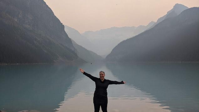 Eveline Lefebvre lève les bras devant un lac, au pied des montagnes Rocheuses.