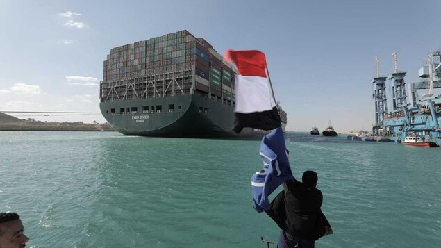 Un homme agite le drapeau égyptien devant le navire.