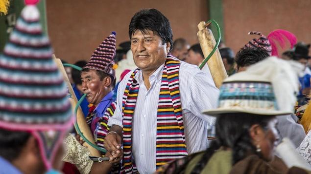Un homme portant une chemise aux manches retroussées et un foulard multicolore danse avec des Boliviens en tenues traditionnelles.
