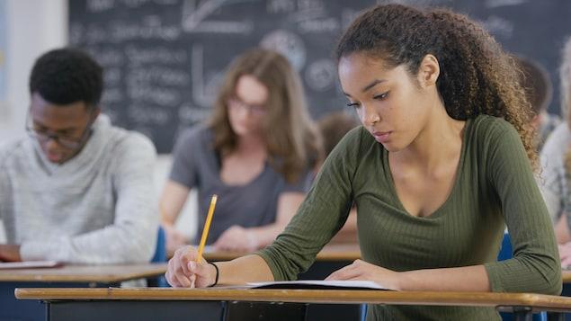 Des élèves répondent aux question d'un examen en classe.