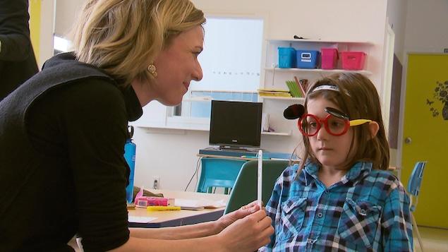 Une jeune fille reçoit un examen de la vue dans une classe lors d'une activité de sensibilisation.