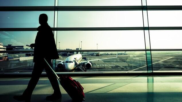Silhouette d'un homme qui marche en tirant une valise dans un couloir d'aéroport vitré avec vue sur des avions stationnés sur la piste.