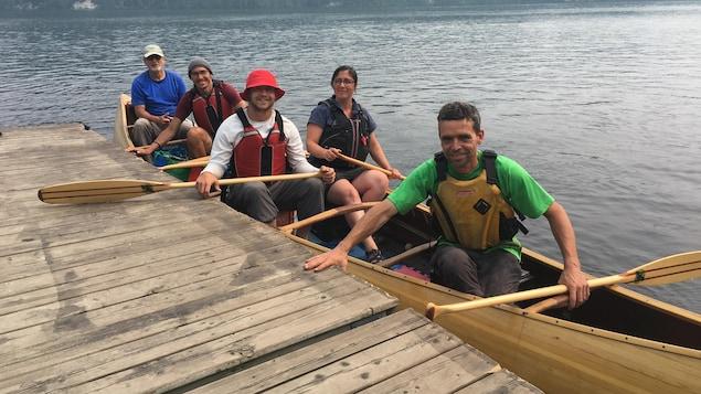 Cinq personnes à bord d'un canot arrivant à quai.