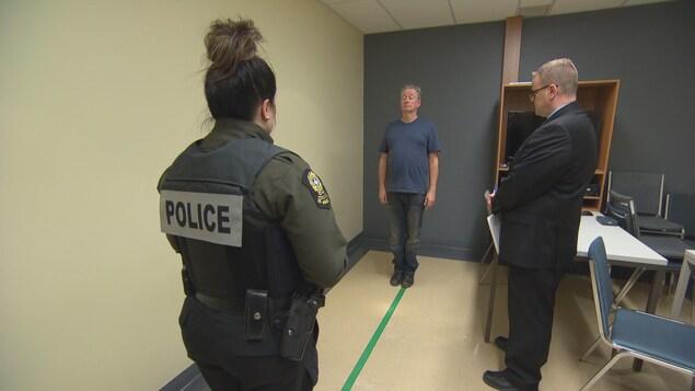 Une policière en formation pour devenir experte en reconnaissance de drogue en compagnie de son instructeur et d'un comédien à l'École nationale de police du Québec à Nicolet.