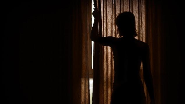 Silhouette d'une femme qui ouvre les rideaux d'une chambre d'hôtel.