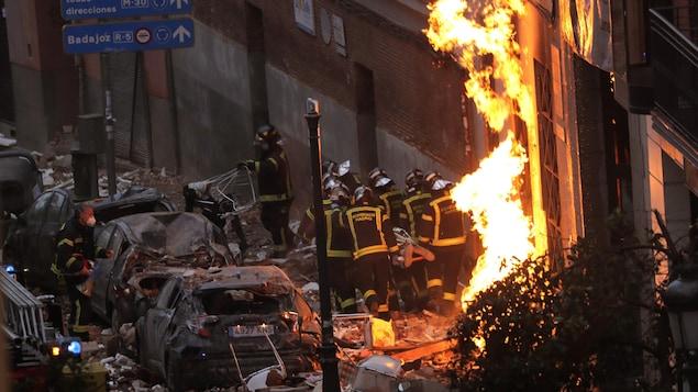 Des pompiers transportent une civière devant la façade l'immeuble détruit.