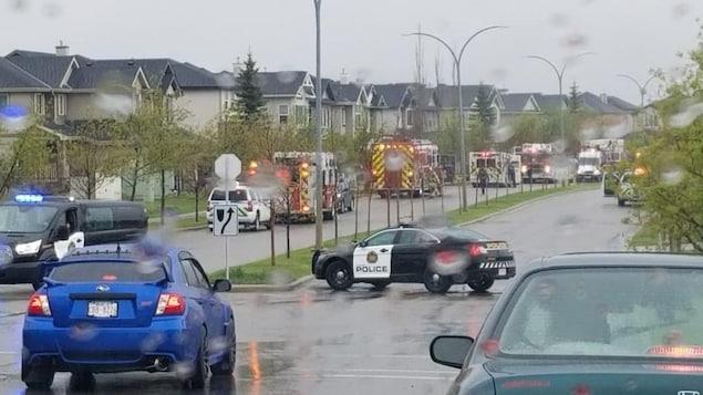 Des véhicules d'urgence garées le long d'une rue sous la pluie.