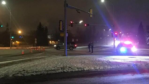 Deux voitures de police bloquent une intersection de routes la nuit en hiver.