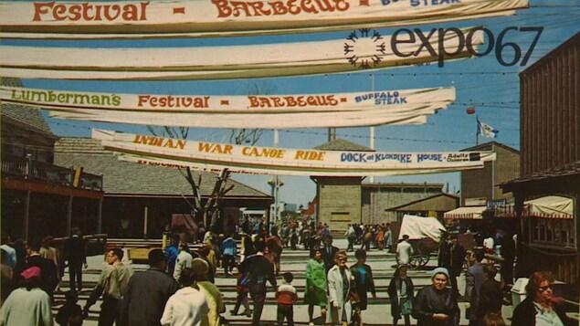 Photo en couleur montrant des dizaines de personnes se promenant sous des banderoles.