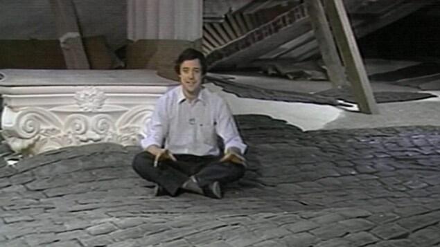Le journaliste Charles Tisseyre assis dans un décor de l'exposition Cités-cinés.