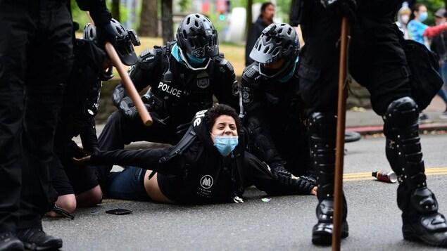 Une personne est couchée sur le sol sous les genoux de deux policiers.