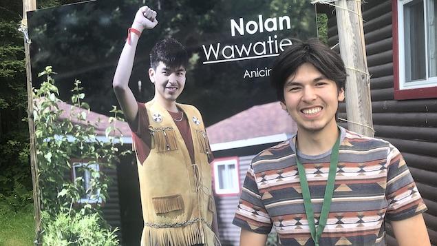 Nolan Wawatie pose devant son affiche dans l'exposition.