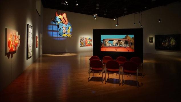 Une salle dans un musée avec de grandes peintures illuminées sur des murs et sur des panneaux.