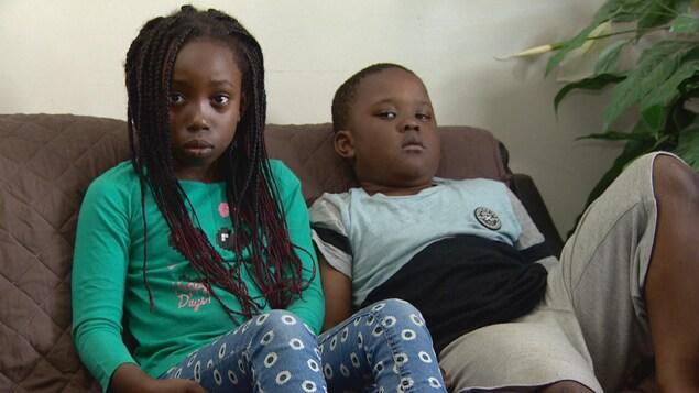 Deux enfants assis sur un canapé.