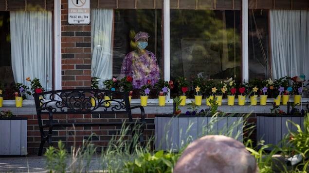Une dame habillée en uniforme d'infirmière regarde à travers la fenêtre.