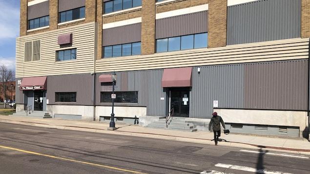 Un homme traverse la rue devant un bâtiment.