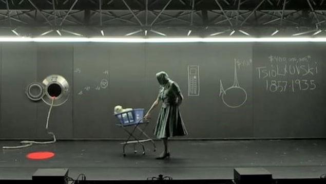 Une femme pousse un bébé dans un carrosse. Sur le mur derrière elle se trouve un dessin de la Terre et un hublot de vaisseau spatial.