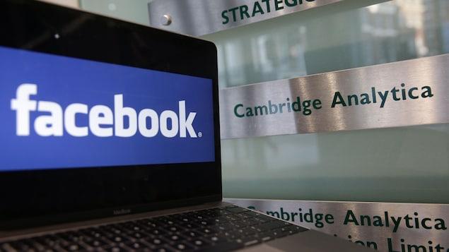 Un ordinateur portable montrant le logo de Facebook est posé à côté d'une plaque indiquant les bureaux de Cambridge Analytica, à Londres, le 21 mars 2018.