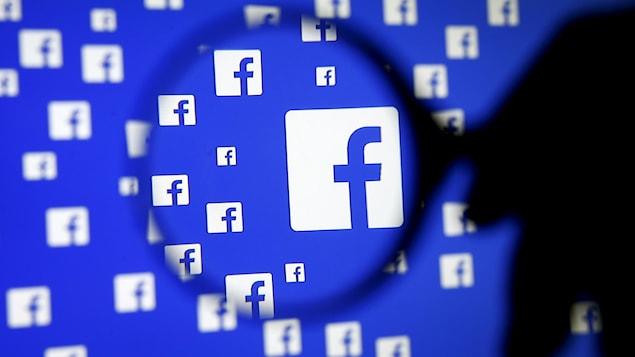 Une loupe devant un logo Facebook