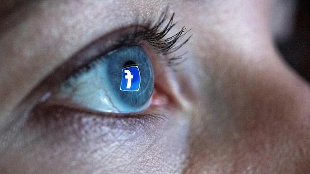 Une femme se tient devant un écran d'ordinateur qui affiche le logo du réseau social Facebook. Ce logo est reflété dans son œil.