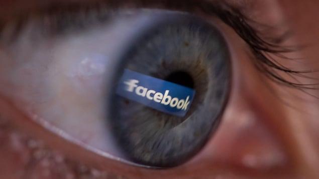 Un œil, vu de proche, avec la réflexion du logo de Facebook.