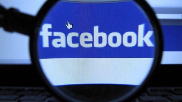 Une loupe grossit le logo de Facebook qui s'affiche sur un écran d'ordinateur.