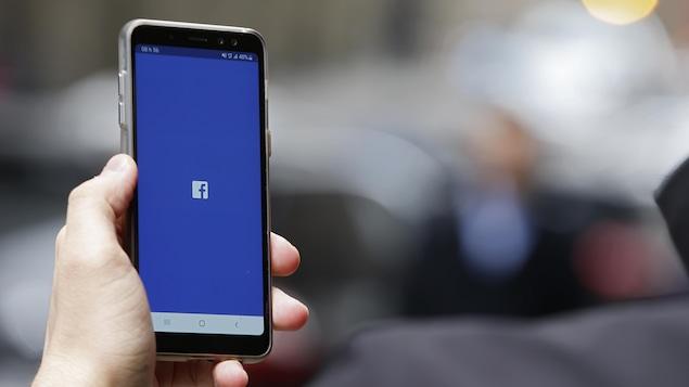 Un écran d'appareil cellulaire affiche le logo de Facebook.