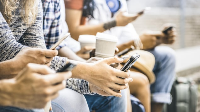 Plusieurs personnes assises manient un téléphone intelligent.