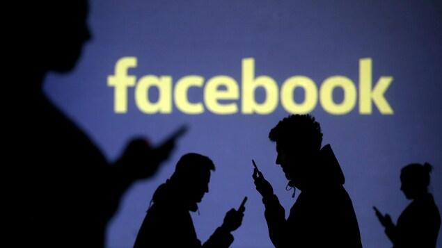 Des personnes regardent leur téléphone avec le logo de Facebook en arrière-plan.