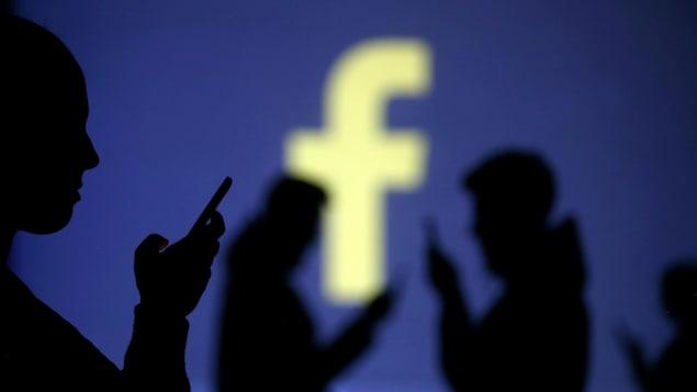 Des silhouettes de personnes qui utilisent des téléphones intelligents sont visibles devant un grand écran qui affiche le logo de Facebook.