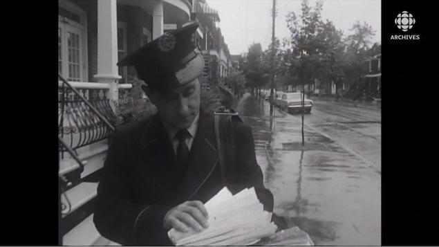 Homme qui regarde des lettre en marchant sur la rue.