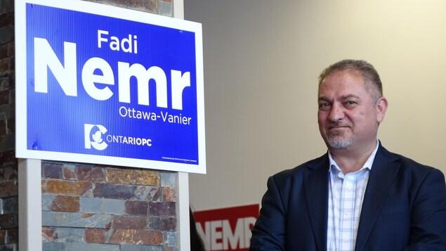 Un homme en veston à côté d'une pancarte électorale