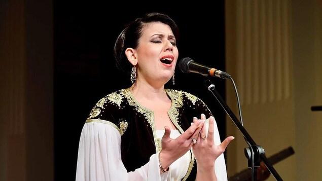 Une femme brune chante devant un micro.