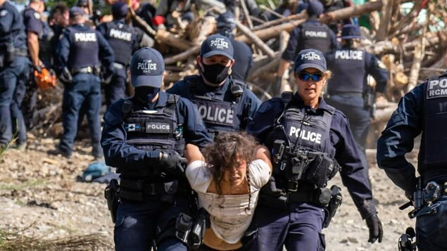 Une femme est transportée par 3 agents de la GRC à Fairy Creek.