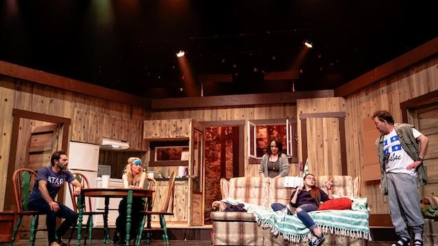 Cinq comédiens prennent place dans un décor évoquant un salon et une cuisine dans un chalet de bois. Un homme et une femme sont assis à une table, à gauche, une adolescente est assise sur le divan, derrière lequel une autre femme se tient debout. Le cinquième acteur est debout à droite, une main à la hanche.