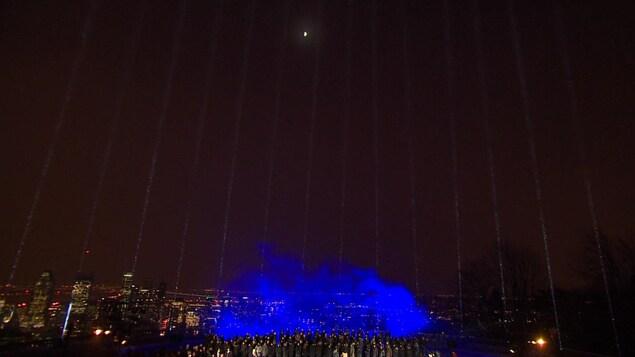 Une foule rassemblée sous les faisceaux lumineux représentant les victimes de Polytechnique.