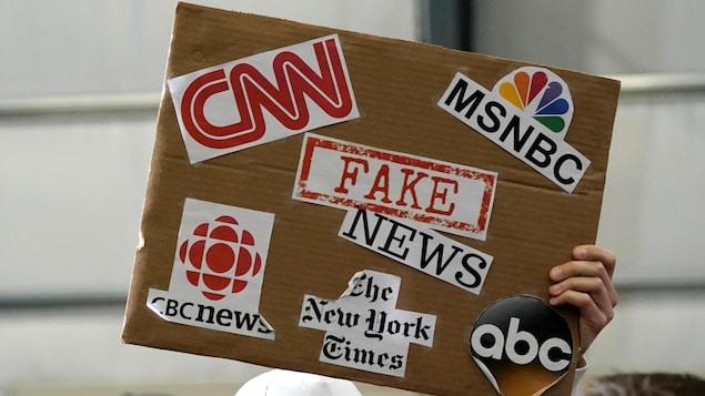 Un partisan du président Donald Trump brandit une pancarte associant les fausses nouvelles à des médias tels que CNN, CBC News et le New York Times.