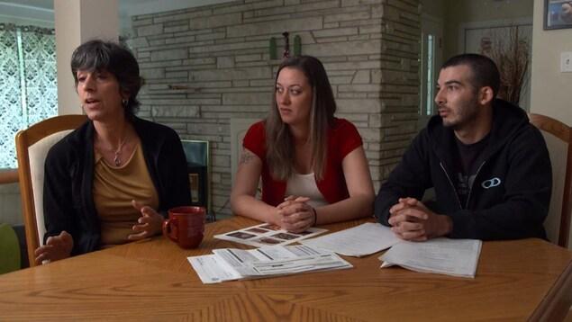 Les trois sont assis autour de la table.