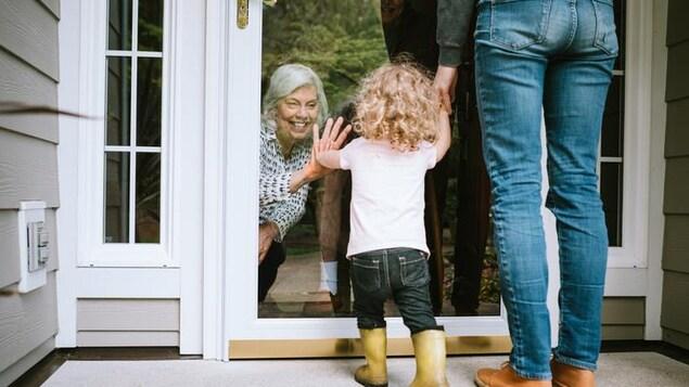 Une petite fille salue sa grand-mère par une fenêtre.