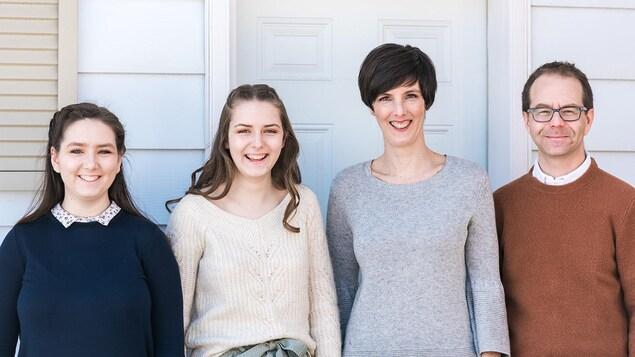 Georgia, Sadie,  et leurs parents Renée et Curtis devant leur maison.
